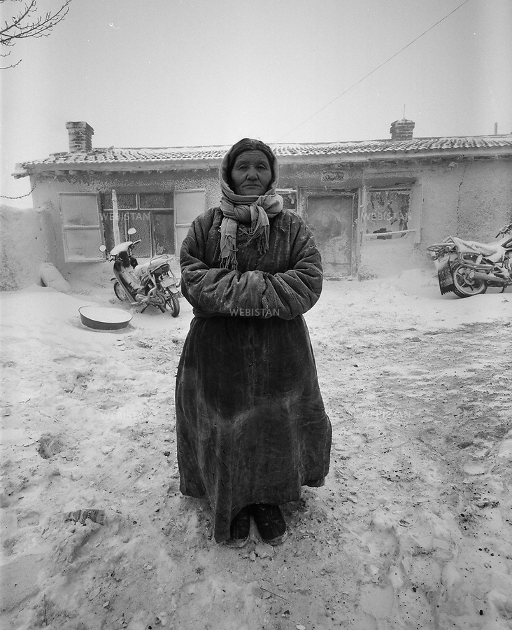 """Inner Mongolia, Xilingol Meng, East Ujimqin Qi, Daotezuo'er Town, Baiyintuga Gacha, April 2008.Wulanfu (age 64)...Wulanfu standing in front of her mud house, crossing her arms in front of her chest..The Mongolians on the grassland all have big kind hearts. Wulanfu is a kind-hearted woman. When the storm of """"Cultural Revolution"""" hit the grassland, all the lamas in the temples were driven out; they had no children, no family to go to. the younger generation who lived on the grassland brought lamas back to their own homes and took care of them. The twenty-three years old Wulanfu and husband E'erdeni brought senior lama Dage home, they had lived together for thirty years until Dage passed away..Wulanfu has 2 sons and 3 daughters, now she lives with first daughter-in-law, enjoy her happy life. She has 2 houses of her own, 121 sheep, 25 cattle and 6 horses. ."""