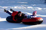 Echo Valley's tubing hill at the Echo Valley Ski area gets a lot of use by families. This father holds on for dear life as his child screams in delight on her ride.