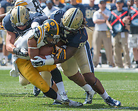Pitt linebacker Matt Galambos (left) and lineman Darryl Render (right) tackle an Iowa ball carrier. Iowa Hawkeyes defeated the Pitt Panthers 24-20 at Heinz Field, Pittsburgh Pennsylvania on September 20, 2014.
