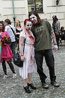 A man and a woman participating in the Zombie Walk in Prague. He is wearing black jeans and a T-shirt, and having make-up blood around the mouth, she is wearing a white dress, black shoes and with make up blood on the dress. She has red hair.