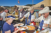 The 21st annual Lincoln County Cowboy Symposium was held in October 2010 at the Ruidoso Downs Racetrack in Ruidoso, New Mexico. Wayne Calk (center,with gloves) serves up food with his crew from the Calk-Clark Wagon out of El Paso, Texas.