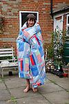 Model released image of teenage boy wrapped in patchwork duvet, UK