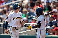 Michigan Wolverines third baseman Blake Nelson (10) is greeted by teammate Aka Thomas (4) after scoring against the Texas Tech Red Raiders in the NCAA College World Series on June 21, 2019 at TD Ameritrade Park in Omaha, Nebraska. Michigan defeated Texas Tech 15-3 and will play in the CWS Finals. (Andrew Woolley/Four Seam Images)