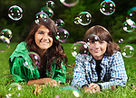 Artistic portrait of two happy smiling children, sister and younger brother, lying down on green grass with soap bubbles around them.