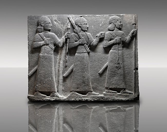 Picture & image of a Neo-Hittite orthostat of 3 warriors from the legend of Gilgamesh from Karkamis,, Turkey. Museum of Anatolian Civilisations, Ankara. The warrior on the far left holds a spear in one hand and the branch of a tree in the other. The middle warrior has a clenched fist an carries an impliment over his shoulder. The warrior on the far right carries a saff. All 3 are wearing swords. 5