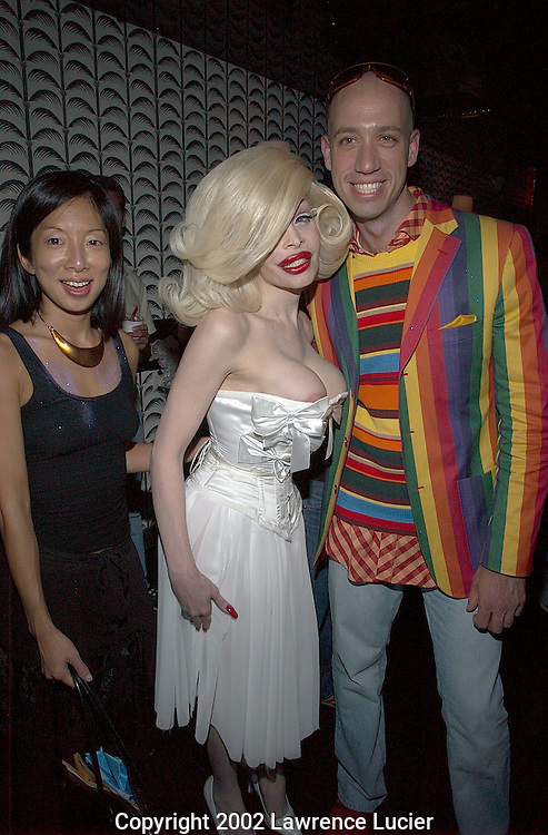 NEW YORK-SEPTEMBER 17: Fashion journalists Christina Ha (L) and Robert Verdi (R) and transexual nightclub fixture Amanda Lepore (center) arrive for the after-party for the Heatherette fashion show at Lounge at elmo September 17, 2002 in New York City.
