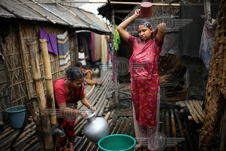 Women washing outside their slum home. The slum population in Dhaka has doubled in a decade to reach 3.4 million in 2006 from only 1.5 million in 1996, following heavy rural-urban migration.