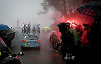 smoke flairs up the extremely wet, cold & misty Cole di Mortirolo <br /> <br /> Stage 16: Lovere to Ponte di Legno (194km)<br /> 102nd Giro d'Italia 2019<br /> <br /> ©kramon