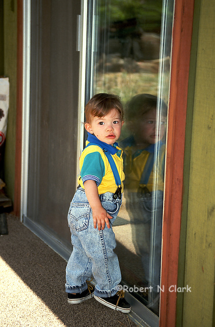 Young boy standing on porch next to glass door looking back at something