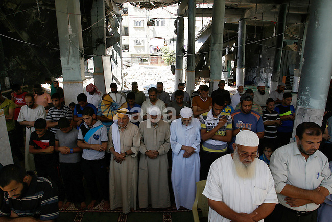 Palestinian Muslims hold noon prayers at the heavily damaged al-Faruq mosque which was destroyed by Israeli strikes during the summer's fierce offensive, in Rafah in the southern Gaza Strip September 21, 2014. Photo by Abed Rahim Khatib