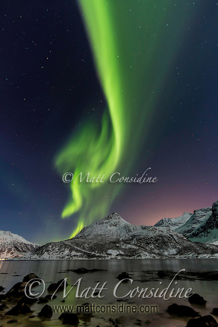 Verticle display of northern lights over mountains and water. (Photo by Travel Photographer Matt Considine).