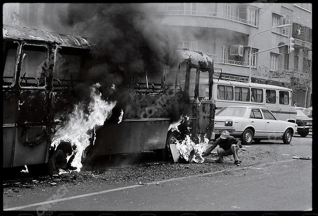 An anti-Shah demonstrator sets a bus afire in downtown Tehran. December 26, 1978.