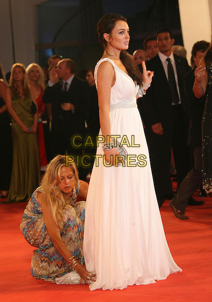 """LINDSAY LOHAN.""""Bobby"""" Premiere during The 63rd International Venice Film Festival held at Palazzo del Cinema, Lido, Italy..September 5th, 2006.Ref: ADM/ZL.full length white dress helper adjusting skirt assistant bending down silver clutch purse.www.capitalpictures.com.sales@capitalpictures.com.©Zach Lipp/AdMedia/Capital Pictures."""