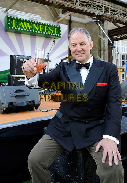 """ANTHONY ADAMS (Frank Sinatra from the BBCs """"The One And Only"""").At """"Lawnfest"""", an open air concert, West Heath School, Sevenoaks, Kent, England..June 25th, 2009.half length black tuxedo glass drink beverage champagne sitting bar .CAP/FIN.©Steve Finn/Capital Pictures."""