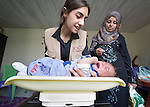 Maha Haidar, a health and nutrition specialist with International Orthodox Christian Charities, a member of the ACT Alliance, weighs five-month old Yasser as his mother Maryam Ismael looks on in the community health center in Kab Elias, a town in Lebanon's Bekaa Valley which has filled with Syrian refugees. Ismael is a Syrian refugee. Lebanon hosts some 1.5 million refugees from Syria, yet allows no large camps to be established. So refugees have moved into poor neighborhoods or established small informal settlements in border areas. International Orthodox Christian Charities provides support for the community clinic in Kab Elias, which serves many of the refugees.