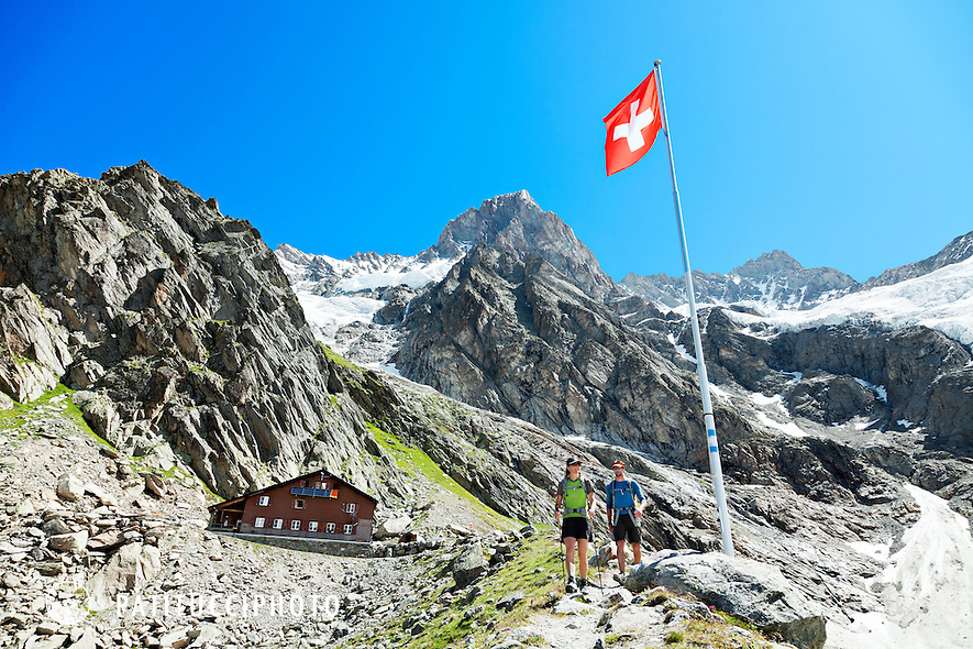 Two hikers leaving the Swiss Alps Shreckhorn Hut in the Berner Oberland, Switzerland