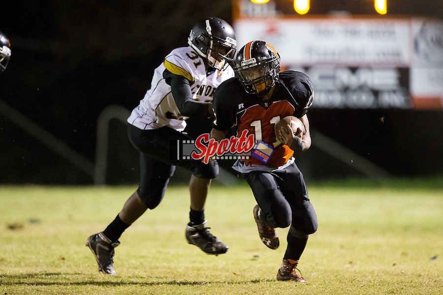 IJ Sturdiant (11) of the Northwest Cabarrus Trojans runs away from Javiare Vaillant (31) of the Concord Spiders during second half action at Trojan Stadium October 29, 2015, in Concord, North Carolina.  The Spiders defeated the Trojans 30-26.  (Brian Westerholt/Sports On Film)