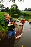 Two young boys releasing a fish after they caught it in a pond in the summer in northeast PA.
