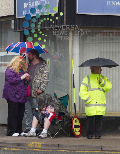 A school boy sleeps as his family wait for the torch through the streets of Stewarton. Scotland has welcomed the Olympic torch for the first time as the relay travels from  to Glasgow on day 21.Picture: Maurice McDonald/Universal News And Sport (Europe). 8 June 2012. www.unpixs.com.