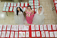 "COPY BY TOM BEDFORD<br /> Pictured L-R: Members of staff Lara Williams, Michelle Curry and Sara Morris who have been trying on some of the dresses at the John Pye Auctions warehouse in Pyle, south Wales, UK.<br /> Re: A bride cried tears of joy after her missing wedding dress was found among a pile of 20,000 gowns in a warehouse.<br /> Meg Stamp, 27, paid £1,300 for the beautiful ivory lace dress but it  was seized by liquidators after a bridal company went bust.<br /> It was boxed up along with 20,000 others and due to be sold for a knock-down price at auction.<br /> But determined Meg banged on the auctioneer door saying: ""I want my dress back"".<br /> Staff at John Pye auctioneers in Port Talbot spent three hours sifting through boxes until they finally found Meg's dream dress."