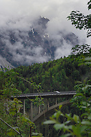 Car travelling on bridge across deep ravine, passing forests and cloud shrouded mountains,Reutte district, Tyrol / Tirol, Austria.