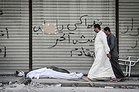Two men pass by walking in front of the dead bodies of Syrian civilians as they lie down on the street outside a hospital after were killed by aircraft shelling in Qadi-Askar neighborhood at the northeast of Aleppo City.