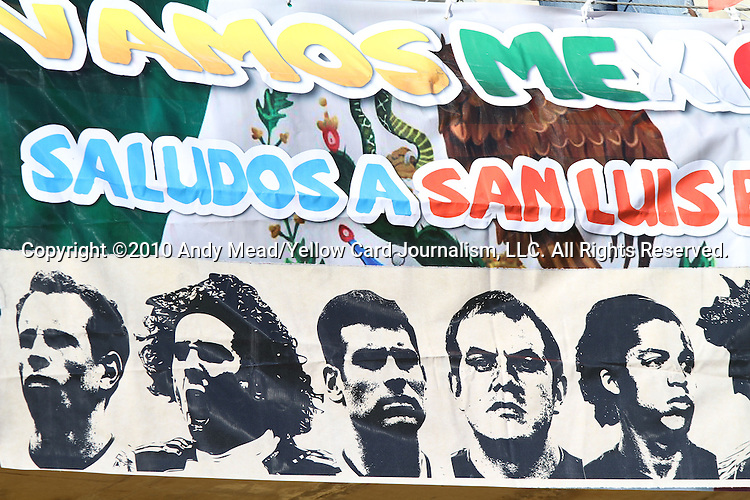 "22 JUN 2010: A sign is displayed over a Mexico flag, reading ""Vamos Mexico - Saludos a San Luis"" and bearing the images of Mexico players. The Mexico National Team played the Uruguay National Team at Royal Bafokeng Stadium in Rustenburg, South Africa in a 2010 FIFA World Cup Group A match."