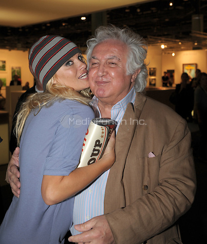 MIAMI BEACH, FL - DECEMBER 06: Pamela Anderson and photographer friend David LaChapelle attend Art Basel 2008. Pam got all excited when she saw what looked like a Christmas ornament in lights that said &quot;happy&quot; she said that's all me and she tried to buy it for half price from the artist. Pam also stopped and posed with a picture of her, but apparently did not have any interest in it other than a photo op. on December 6, 2008, at the Miami Beach Convention Center in Miami Beach, Florida.<br /><br /><br />People:  Pamela Anderson, Tony Shafrazi<br /><br />Transmission Ref:  FLXX<br />Credit: Hoo-Me.com / MediaPunch