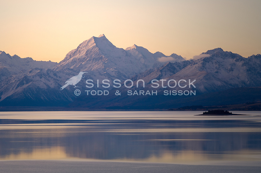 Aoraki Mount cook is reflected in lake pukaki after sunset.  The southern alps are shown in their full beauty..