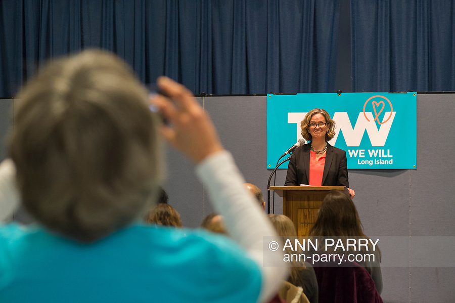 Wyandanch, New York, USA. March 26, 2017. At podium, LAURA CURRAN, Nassau County Legislator (Dem - District 5) speaks at Politics 101 event, the first of series of activist training workshops for members of TWW LI, the Long Island affiliate of national Together We Will. Member wearing blue TWWLI shirt takes cell phone photo of speaker. Curran is candidate for Nassau County Executive. One of the 5 speakers referred to groups such as TWWLI as activist pop-up groups.