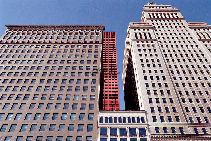 "Symmetrical pattern on the facade of some older buildings alongside of Michigan Ave.  The architecture of Chicago has influenced and reflected the history of American architecture. The city of Chicago, Illinois features prominent buildings in a variety of styles by many important architects. Since most buildings within the downtown area were destroyed by the Great Chicago Fire in 1871, Chicago buildings are noted for their originality rather than their antiquity..Beginning in the early 1880s, architectural pioneers of the Chicago School explored steel-frame construction and, in the 1890s, the use of large areas of plate glass. These were among the first modern skyscrapers and amongst their most famous architects were William LeBaron, John Wellborn Root Sr., Daniel Burnham and Charles Atwood. Louis Sullivan was perhaps the city's most philosophical architect. Realizing that the skyscraper represented a new form of architecture, he discarded historical precedent and designed buildings that emphasized their vertical nature. This new form of architecture, by Jenney, Burnham, Sullivan, and others, became known as the ""Commercial Style,"" but it was called the ""Chicago School"" by later historians..Since 1963, a ""Second Chicago School"" emerged, largely due to the ideas of structural engineer Fazlur Khan. Some of Chicago's skyscrapers such as the John Hancock Center, Willis Tower (formerly known as the Sears Tower) and The Trump International Hotel and Tower are amongst the tallest uildings in the world."