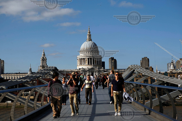 People cross the Millennium Bridge in front of St Paul's Cathedral, London.