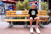 11 year old child sitting outside Bubba Gump restaurant in Kailua-Kona. Kona, Big Island, Hawaii