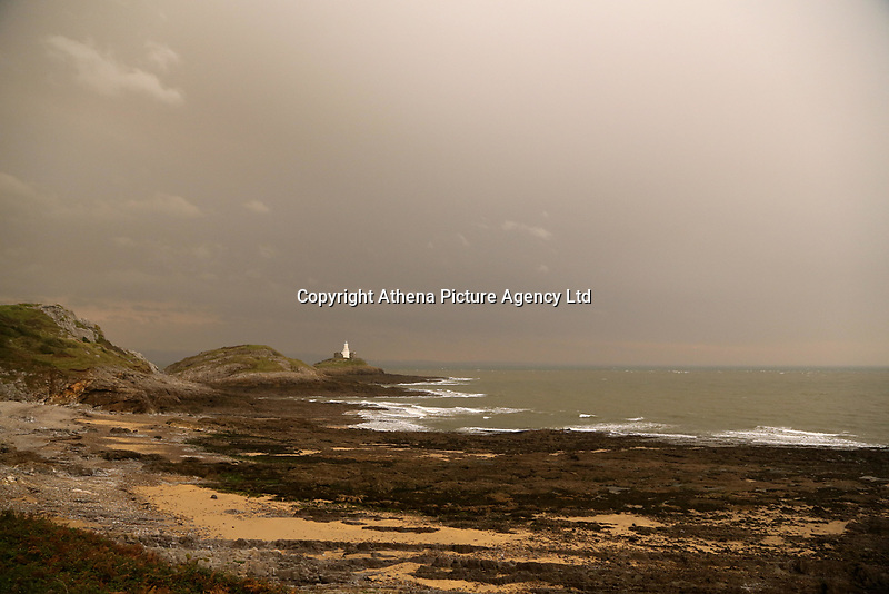 "An unusually orange cloud over Mumbles Lighthouse at the seaside village of Mumbles near Swansea, UK. Monday 16 October 2017<br /> Re: Remnants of Hurricane Ophelia are expected to bring strong gusts of wind to Wales when it hits Britain's shores.<br /> The hurricane, making its way from the Azores in the Atlantic Ocean, will have weakened to a storm when it arrives.<br /> A Met Office amber ""be prepared"" warning has been issued in some areas bringing ""potential danger to life""."