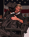 Photo by Phil Grout..North Carroll High School principal Kimberly Dolch leans over and.congratulates Joe Bulls moments after he receives his diploma in spite of.his ongoing battle with MS.