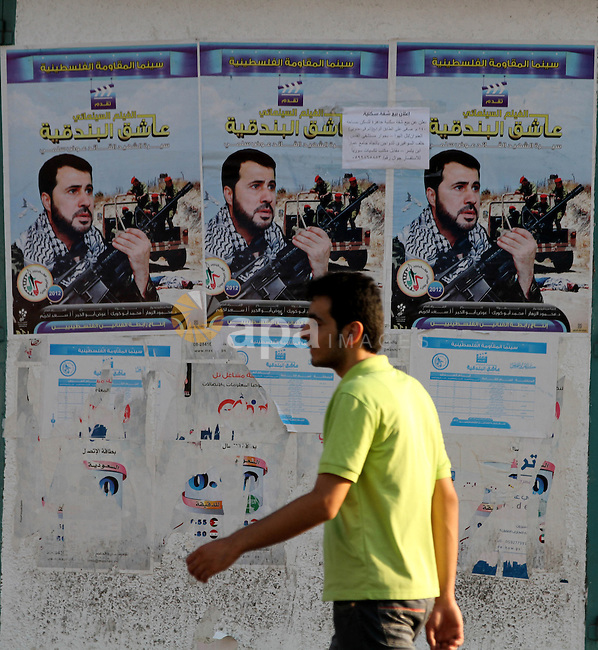 A Palestinian man walks pass a poster with a picture for cinema movie about the life of the leader in Izz al-Din al-Qassam, the military wing of hamas, the martyr Awad Silmi, in Gaza city, on Aug 28, 2012. Hamas prepare to show a series about the life of Hamas leader Sheikh Ahmed Yaseen next Ramadan. Photo by Majdi Fathi