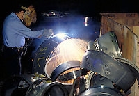 Titanium, rejected aircraft engine parts being cut by a worker with cutting torch, horz. Hartford CT USA.