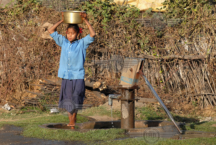 A young girl in her school uniform carries water on her head from the village pump at Bendri Village in the Urla Industrial Complex.