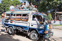 Myanmar, Burma.  Mingun, near Mandalay.  Local Bus Transport.  No Road-Safety Rules Prevent Passengers from Riding on Top.