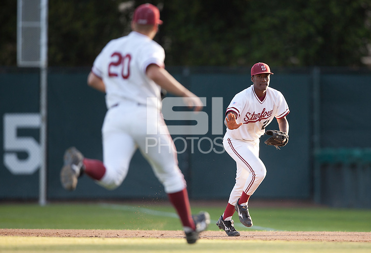 STANFORD, CA - April 12, 2011: Brian Ragira of Stanford baseball waves off pitcher Elliott Byers for the force out at first during Stanford's game against Pacific at Sunken Diamond. Stanford won 3-1.