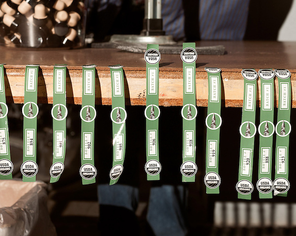 June 18, 2013. Chapel Hill, North Carolina<br />   Gin bottle labels, showing the product's organic designation, await bottled liquor.<br />  TOPO, Top of the Hill Distillery, the brainchild of owner Scott Maitland and Spirit Guide Esteban McMahan, is located in the old N&amp;O Building on Franklin Street. Making gin, vodka and American whiskey from locally sourced wheat, they are one of the few distilleries bringing  organic liquor to ABC shelves around the state.