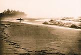 USA, Hawaii, surfer going towards the water, Sunset Beach (B&W)