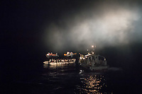 Die Sea Watch-2 Crew war am Freitag den 21. Oktober 2016 in den fruehen Morgenstunden waehrend ihrer 13. SAR-Mission vor der libyschen Kueste zu einer Position ausserhalb der 12 Meilenzone gerufen worden. Es war ein Fluechtlingsschlauchboot gesichtet worden. Als die Sea Watch-2 dort eintraf sah sie ca. 150 Menschen zusammengepfercht in einem ueberfuellten Schlauchboot sitzen. Eine Versorgung der Menschen auf dem Fluechtlingsschlauchboot mit Rettungswesten durch die Rettungs Boote der Sea Watch-2 wurde von der libyschen Kuestenwache unterbunden. Ein Soldat der Kuestenwache enterte das Schlauchboot vom Bug und machte sich dann an dem Aussenbordmotor zu schaffen. Auf dem Weg dahin schlug und trat er die Gefluechteten ein. Nach einigen Minuten entfernte sich das Boot der Kuestenwache. Dann verlor der Bug des Schlauchbootes seine Luft und es brach Panik bei den Gefluechteten aus. Sie sprangen in das Wasser und versuchten zum Schiff Sea Watch-2 zu gelangen. Die Crew warf ihnen Schwimmwesten und Rettungsringe zu, die Besatzungen der Rettungsboote der Sea Watch-2 zogen Menschen aus dem Meer, dennoch sind bis zu 30 Menschen ertrunken. Vier Ertrunkene konnten von der Sea Watch geborgen werden.<br /> Im Bild: Die Libysche Kuestenwache (rechts), das Fluechtlingsboot und die Rettungsboote der Sea Watch-2 mit Schwimmwesten. Der Soldat der Kuestenwache macht sich am Aussenbordmotor zu schaffen.<br /> 21.10.2016, Mediterranean Sea<br /> Copyright: Christian-Ditsch.de<br /> [Inhaltsveraendernde Manipulation des Fotos nur nach ausdruecklicher Genehmigung des Fotografen. Vereinbarungen ueber Abtretung von Persoenlichkeitsrechten/Model Release der abgebildeten Person/Personen liegen nicht vor. NO MODEL RELEASE! Nur fuer Redaktionelle Zwecke. Don't publish without copyright Christian-Ditsch.de, Veroeffentlichung nur mit Fotografennennung, sowie gegen Honorar, MwSt. und Beleg. Konto: I N G - D i B a, IBAN DE58500105175400192269, BIC INGDDEFFXXX, Kontakt: post@christian-ditsch.de<br /> Be