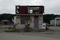A landscape view of a damaged building and a Japanese Flag at Miyako Bay during reconstruction efforts following the 311 Tohoku Tsunami in Miyako, Japan  © LAN
