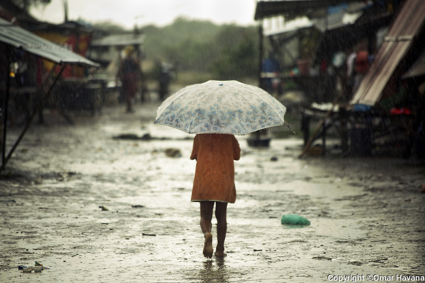 SIEM REAP, CAMBODIA. One of the children comes back to the shelter of his home with the arrival of the rain of the Cambodian monsoon under a huge umbrella.  Almost 200 people live in a community on the shore of the Tonle Sap Lake, just few kilometers away from the city of Siem Reap, home to the world famous temples of Angkor. With the arrival of the wet season, the community is forced to move their homes up to the Phnom Krom Mountain where the water of the Tonle Sap Lake will not rise and cover their entire village. Photo: ©Omar Havana