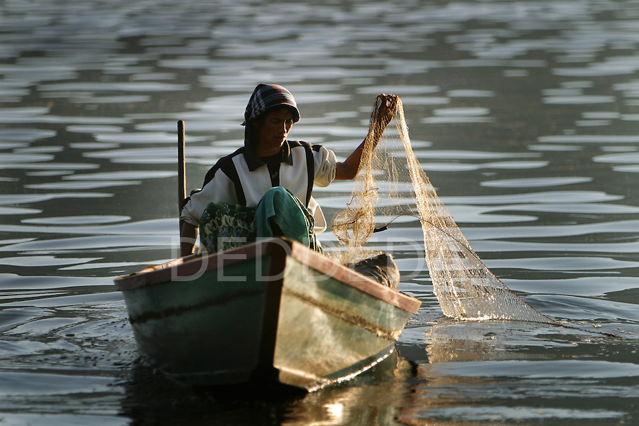A woman checks her fishing nets as the sun sets on Phewa Tal, or Fewa Lake, in Pokhara, Nepal.