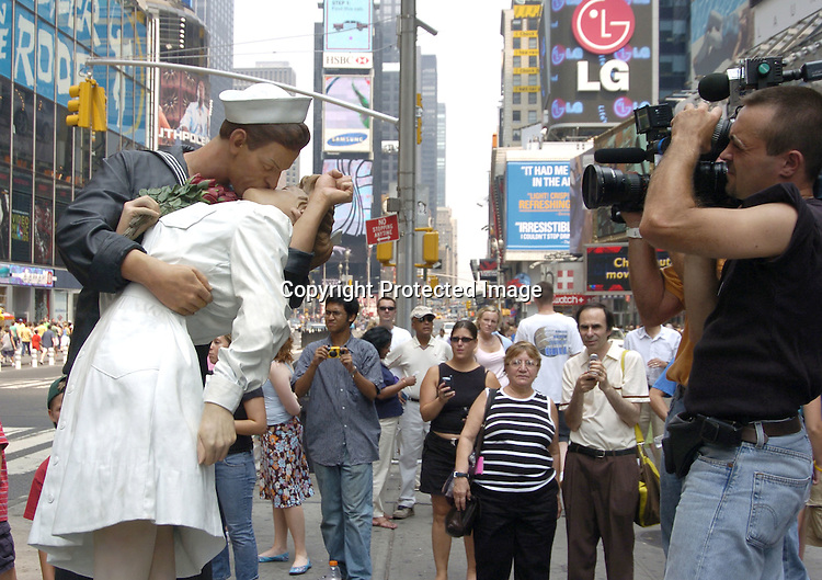 The Unconditional Surrender Sculpture by Seward Johnson ..and a camera crew ..at the 60th Anniversary of the end of World War II in Times Square in New York City on August 14, 2005. Edith and Carl  were the couple in the Alfred Eisenstadt photograph celebrating the Allied Victory in the War. ..Photo by Robin Platzer, Twin Images