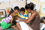 Education Preschool 3-5 year olds female student teacher reading book to two boys and a girl horizontal