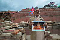 Nepal, Kathmandu, earthquake damage at Kathmandu Durbar Square. Man holding my photo of the where the same actual 16th century Hindu temple once stood. Man holding Nepali flag.