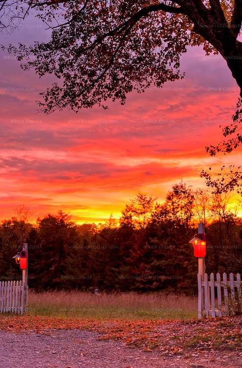 A brilliant sunset backlights an illuminated farm fence at High Meadows Vineyard Inn.